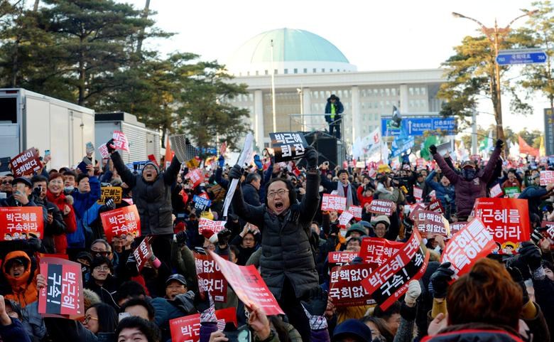 People react after impeachment vote on South Korean President Park Geun-hye was passed, in front of the National Assembly in Seoul, South Korea, December 9, 2016. The sign reads ''Impeach Park Geun-hye''.  News1 via REUTERS