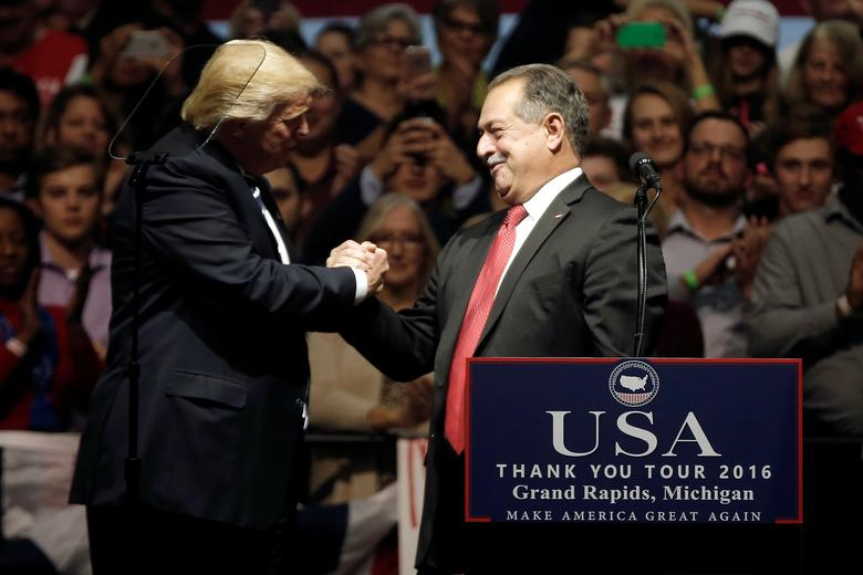 U.S. President-elect Donald Trump greets Andrew Nicholas Liveris, Chairman and chief executive officer of The Dow Chemical Company to the stage at a ''Thank You USA'' tour rally in Grand Rapids, Michigan, U.S. December 9, 2016.  REUTERS/Mike Segar