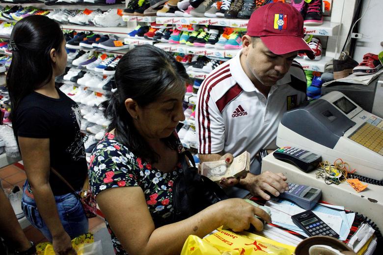 People pay using 100 bolivar notes at a shoe shop in San Cristobal, Venezuela, December 12, 2016. REUTERS/Carlos Eduardo Ramirez
