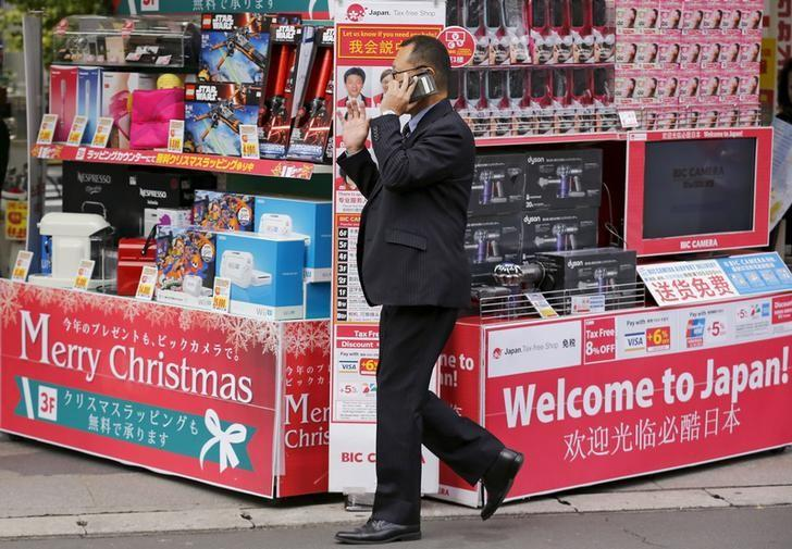 A man talks on the phone as he walks past the Bic Camera consumer electronics retailer in Tokyo, November 26, 2015. REUTERS/Thomas Peter