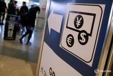 Указатель на пункт обмена валюты в аэропорту Нарита близ Токио 25 марта 2016 года. Доллар стабилизировался на торгах вторника по отношению к иене и евро, в то время как рост доходности гособлигаций США замедлился, и рынок ждет результатов заседания ФРС, которое начнется позднее сегодня. REUTERS/Yuya Shino/File Photo