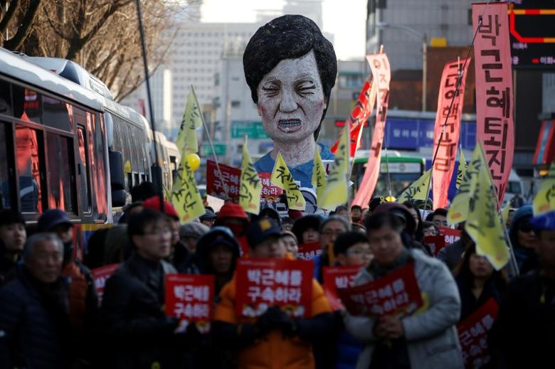 An effigy of South Korean President Park Geun-hye is seen behind people marching towards the Presidential Blue House during a protest calling for South Korean President Park Geun-hye to step down in central Seoul, South Korea, December 10, 2016. The signs read, ''Arrest Park Geun-hye''.  REUTERS/Kim Hong-Ji