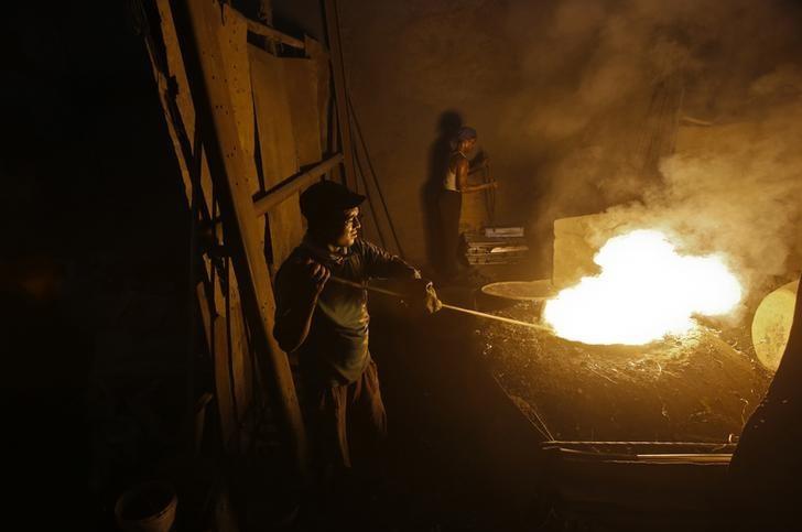 Labourers work inside an aluminium smelting factory in Mumbai March 12, 2013. REUTERS/Vivek Prakash/Files