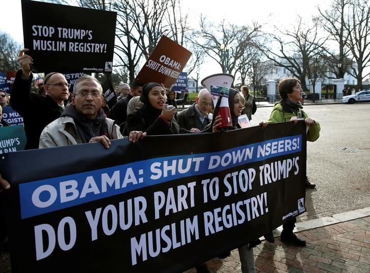 Members of Join MoveOn and DRUM march past the White House during a protest to shut down the existing Muslim registry program NSEERS in Washington U.S., December 12, 2016.    REUTERS/Gary Cameron