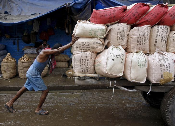 A labourer pushes a handcart loaded with sacks containing tea packets, towards a supply truck at a wholesale market in Kolkata, India, June 26, 2015. REUTERS/Rupak De Chowdhuri