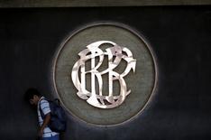 Un hombre pasa por delante del logo del Banco Central del Perú (BCRP) en el centro de Lima. 7 de abril 2015. La economía peruana creció un 2,12 por ciento interanual en octubre, a su menor ritmo mensual en un año y medio, debido a que la expansión de la clave producción minera fue opacada por una caída del sector de la construcción, dijo el jueves el Gobierno. REUTERS/Mariana Bazo - RTR4WG2K