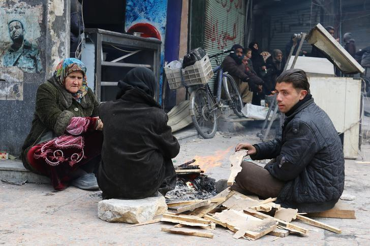 People warm themselves around a fire while waiting to be evacuated from a rebel-held sector of eastern Aleppo, Syria December 17, 2016. REUTERS/Abdalrhman Ismail