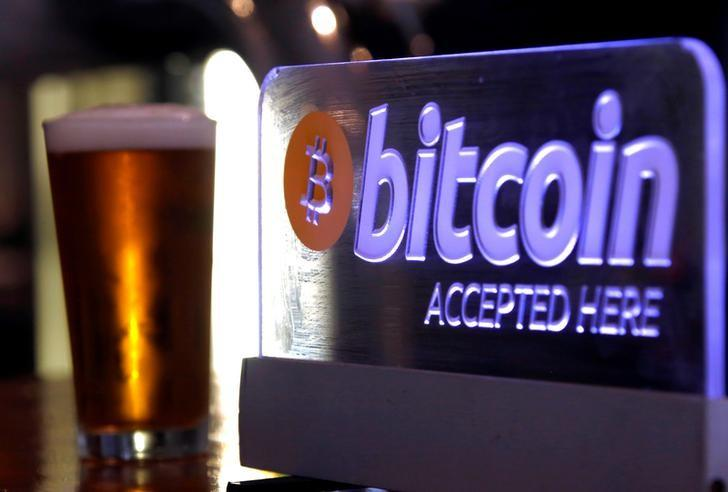 A beer sits next to a Bitcoin sign on display at a bar in central Sydney, Australia, September 29, 2015.  REUTERS/David Gray/Files