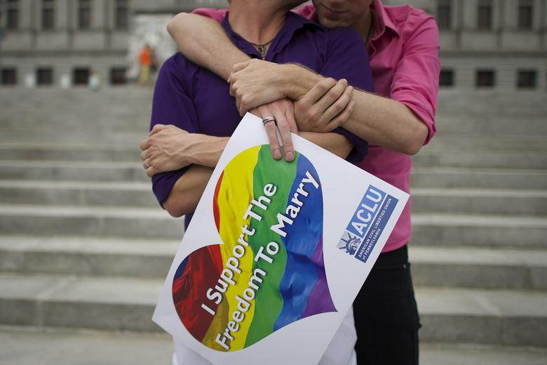 A couple embrace on the Pennsylvania State Capital steps following a rally with gay rights supporters after a ruling struck down a ban on same sex marriage in Harrisburg, Pennsylvania, May 20, 2014.    REUTERS/Mark Makela/Files
