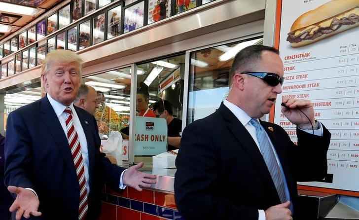 A Secret Service agent keeps watch as Republican presidential nominee Donald Trump (L) makes a stop at Geno's Steaks cheesesteak restaurant in Philadelphia, Pennsylvania, U.S. September 22, 2016. REUTERS/Jonathan Ernst/File Photo