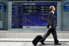 Un hombre pasa por delante de una tabla electrónica que muestra el promedio del Nikkei fuera de una correduría en Tokio, Japón, 1 de abril 2016. El índice Nikkei de la bolsa de Tokio bajó el miércoles en una sesión volátil luego de que los inversores recogieron ganancias antes de los feriados de Navidad. REUTERS/Thomas Peter - RTSD3HP