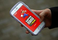 "Takuya Nishya shows Nintendo's ""Super Mario Run"" game on his smartphone by the request of a photographer in Tokyo, Japan, December 20, 2016.  REUTERS/Kim Kyung-Hoon"