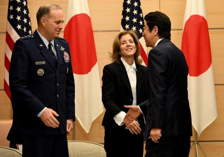 Japanese Prime Minister Shinzo Abe (R) reaches his hand towards US Forces Japan commander Lieutenant General Jerry P. Martinez (L) while US Ambassador to Japan Caroline Kennedy (C) looks on during a joint announcement on the return of American military to the island of Okinawa at the Abe's official resident in Tokyo on December 21, 2016.  REUTERS/Toshfumi Kitamura/Pool