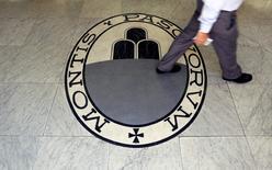 Las dos cámaras del Parlamento italiano aprobaron el miércoles la petición del Gobierno de elevar el endeudamiento hasta en 20.000 millones de euros (20.800 millones de dólares) para apuntalar al frágil sector bancario del país, lastrado por créditos morosos. En la imagen, un hombre camina sobre el logo del Monte Dei Paschi Di Siena en Roma, el 24 de septiembre de  2013.  REUTERS/Alessandro Bianchi/File Photo