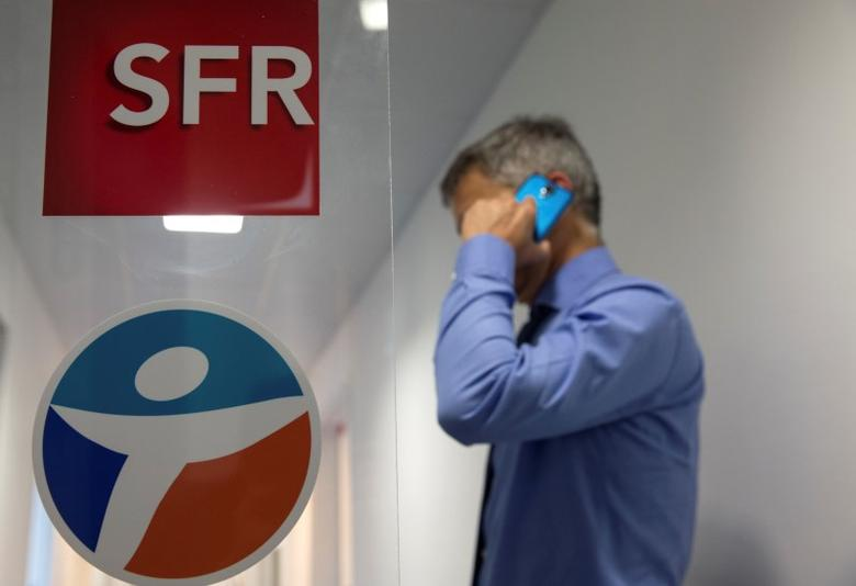 A photo illustration shows a man making a phone call as he stands near logos of French Telecom operators SFR and Bouygues Telecom at the offices of a telecom company in Suresnes near Paris, France, June 23, 2015.   REUTERS/Philippe Wojazer