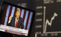 Una pantalla de televisión que muestra al presidente electo de Estados Unidos, Trump, atrás está el índice alemán de precios de las acciones DAX en Francfórt, Alemania. 9 de noviembre 2016.La tenencia de acciones por parte de los inversores globales se elevó a máximos de seis meses en diciembre por apuestas de que el prometido aumento del gasto fiscal del presidente electo, Donald Trump, acelerará el crecimiento y la inflación, indicó un sondeo mensual de Reuters el jueves. REUTERS/Kai Pfaffenbach