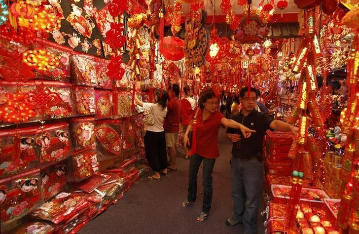 People shop for Chinese New Year decorations at a store in Singapore's Chinatown January 14, 2009. REUTERS/Tim Chong/Files
