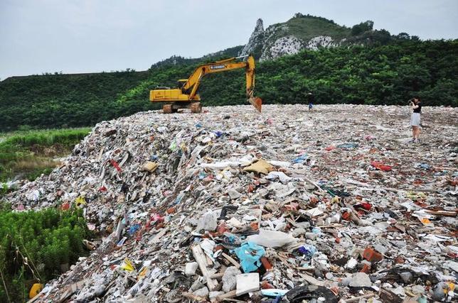 12月25日、中国の立法機関、全国人民代表大会(全人代)は、同国初となる環境保護税を2018年から導入する法案を可決した。  写真は江蘇省蘇州市太湖付近に棄てられた廃棄物の山。 7月に撮影された提供写真(2016年 ロイター)