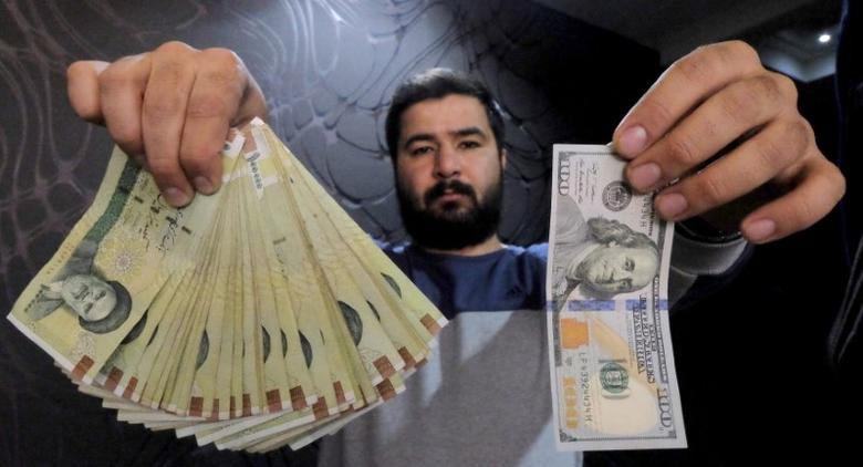 A money changer poses for the camera with a U.S  hundred dollar bill (R) and the amount being given when converting it into Iranian rials (L), at a currency exchange shop in Tehran's business district, Iran, January 20, 2016. REUTERS/Raheb Homavandi/TIMA
