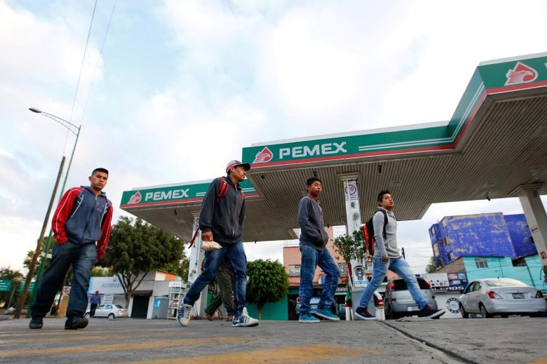 Men walk pass a petrol station with the Pemex logo in Mexico City, Mexico October 13, 2016.  REUTERS/Carlos Jasso