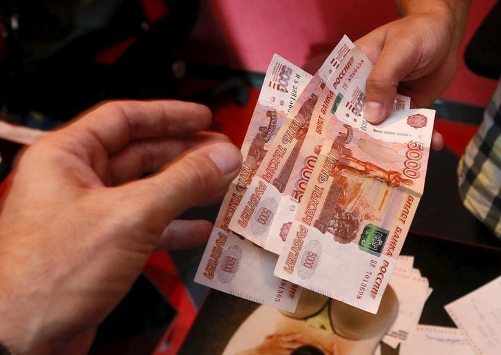 An employee (R) of a car service station takes Russian rouble banknotes from a client in the Siberian city of Krasnoyarsk, Russia, August 6, 2015. REUTERS/Ilya Naymushin