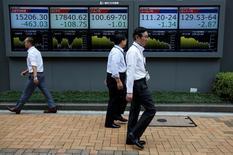 Peatones caminan frente a unas pantallas que muestra el índice Nikkei y otras divisas afuera de una correduría en Tokio, Japón. 6 de julio de 2016. El promedio referencial de acciones japonés Nikkei cerró el miércoles con una baja de 0,01 por ciento, a 19.401,72 unidades, mientras que el índice más amplio Topix subió un 0,04 por ciento, a 1.536,80 unidades. REUTERS/Issei Kato