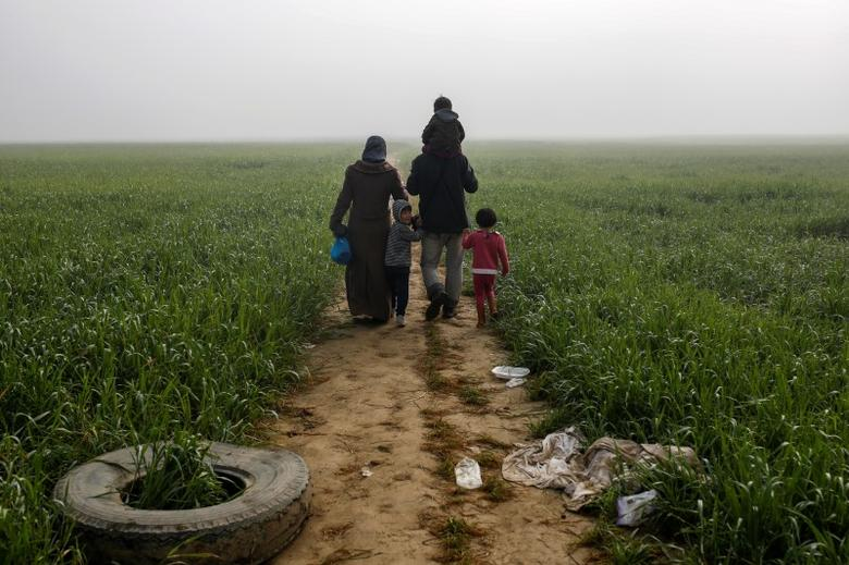 FILE PHOTO -  A family walks through a field at a makeshift camp for migrants and refugees at the Greek-Macedonian border near the village of Idomeni, Greece, April 4, 2016. REUTERS/Marko Djurica/File Photo