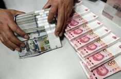 """Imagen de archivo de un cajero contando dólares y yuanes en una sucursal del Banco de China en Taiyuan, en la provincia de Shanxi. 4 enero 2016. El banco central de China rechazó el miércoles un reporte de prensa de que el yuan se había devaluado a menos de 7 unidades por dólar en el mercado local el 28 de diciembre, una publicación que consideró """"irresponsable"""". REUTERS/Jon Woo"""
