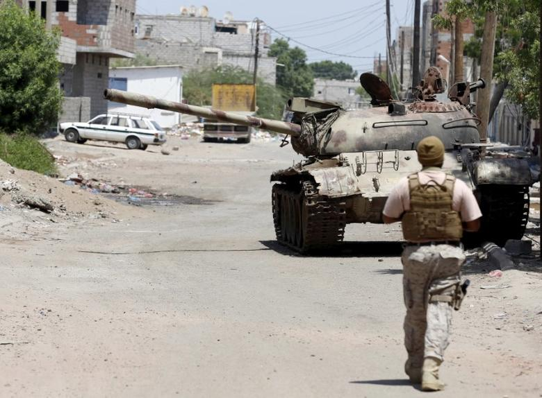 A soldier from the Saudi-led coalition walks past a broken-down tank on a street in Yemen's southern port city of Aden September 27, 2015. REUTERS/Faisal Al Nasser