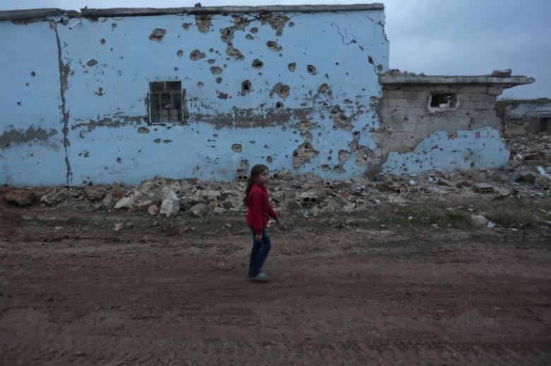 A girl walks near a damaged house in al-Rai town, northern Aleppo province, Syria December 27, 2016. REUTERS/Khalil Ashawi