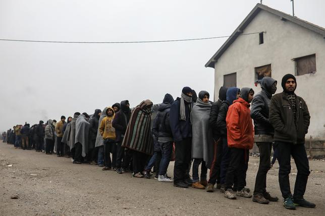 Migrants stand in line to receive free food outside a derelict customs warehouse in Belgrade, Serbia, December 22, 2016. REUTERS/Marko Djurica