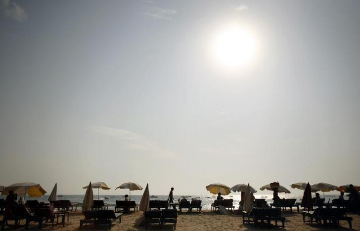Tourists relax under umbrellas at the Baga beach in Goa March 11, 2008. REUTERS/Punit Paranjpe/File Photo