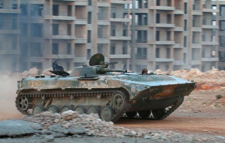 A fighter of the Syrian Islamist rebel group Jabhat Fateh al-Sham rides in an armored vehicle in the 1070 Apartment Project area in southwestern Aleppo, Syria August 5, 2016. REUTERS/Ammar Abdullah/File Photo