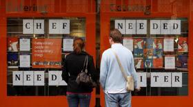 """Los peatones leen anuncios de contratación en el centro de Londres. 15 de octubre 2008. La economía británica terminó 2016 en un pie sólido y registró su crecimiento más veloz desde mediados de 2015, pese a que las empresas enfrentaron una de las alzas de costos más veloces en los últimos cinco años ante la debilidad de la libra esterlina tras el """"Brexit"""", mostró un sondeo de la industria. REUTERS/Alessia Pierdomenico/File Photo"""