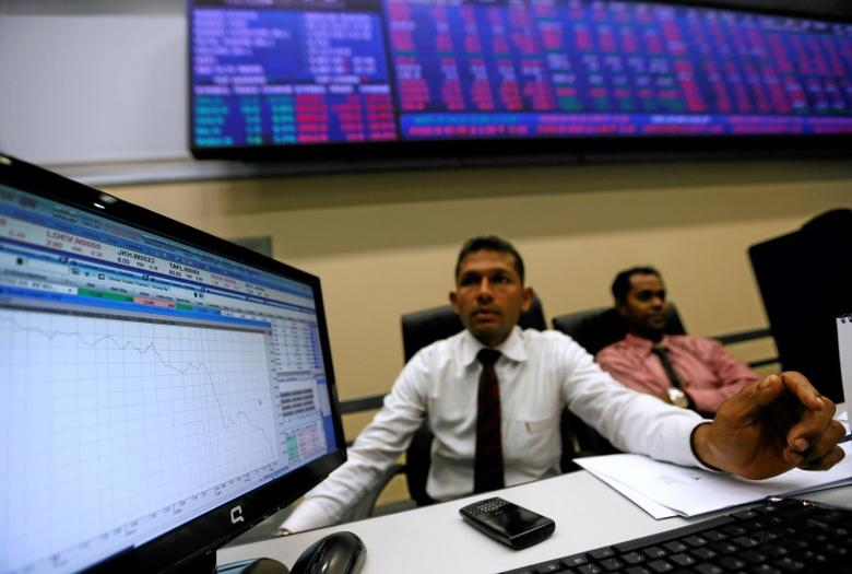 A broker looks at a computer screen showing the movement of the market since the morning opening, at the Colombo Stock Exchange in Sri Lanka March 9, 2016. REUTERS/Dinuka Liyanawatte/File Photo