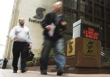 People walk by a sign displaying TSX information in Toronto September 29, 2008. REUTERS/Mark Blinch