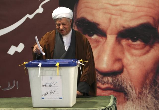 Former Iranian President Akbar Hashemi Rafsanjani casts his ballot in a parliamentary election in Tehran March 2, 2012. In the background is a poster of Ayatollah Ruhollah Khomeini, the late founder of the Islamic Republic. REUTERS/Stringer
