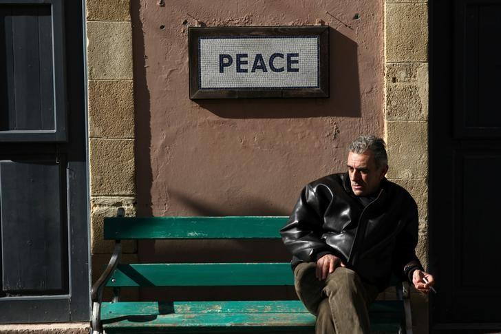 A man sits on a bench under a peace sign near the UN-controlled buffer zone in Nicosia, Cyprus January 9, 2017. REUTERS/Yiannis Kourtoglou