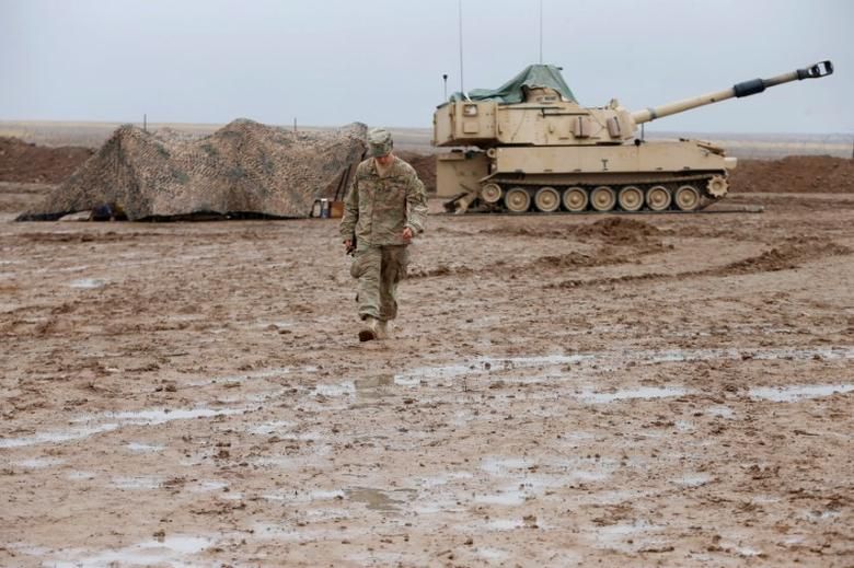 A U.S. soldier walks in front of a tank at an army base in Karamless town, east of Mosul, Iraq, December 25, 2016. Picture taken December 25, 2016. REUTERS/Ammar Awad