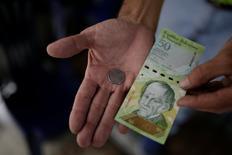 Un comerciante sostiene una moneda de 50 bolívares y un billete de 50 bolívares para esta fotografía tomada en un puesto callejero en el centro de Caracas, Venezuela. 29 de diciembre de 2016. El Gobierno socialista de Venezuela reabrirá la compra y venta de divisas en la frontera con Colombia, buscando detener el alza del dólar en un mercado operado por particulares en el país vecino, dijo el lunes el presidente Nicolás Maduro.  REUTERS/Marco Bello