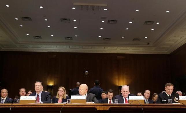 1月10日、トランプ次期米大統領に対してクラッパー米国家情報長官ら情報機関幹部が先週に説明を行った機密文書に、ロシアの諜報員がトランプ氏に関する不利な情報を取得したと主張しているとの指摘が含まれていた。写真左からジェームス・コミ―FBI長官、ジェームス・クラッパー国家情報長官、ジョン・ブレナン中央情報局長官、マイケル・ロジャース国家安全保障局長。ワシントン・議会議事堂で行われた下院委員会証言で撮影(2017年 ロイター/Joshua Roberts)