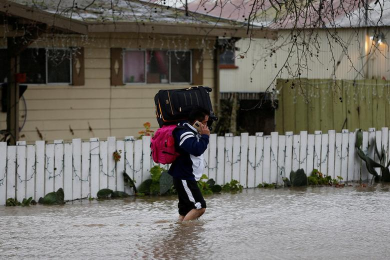 File Photo: Cesar Belvasco walks through a flooded road while carrying his belongings after his home was flooded by the overflowing Petaluma River during a winter storm in Petaluma, California, January 8, 2017. REUTERS/Stephen Lam/File Photo