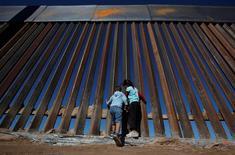 Дети играют около свежепостроенного участка стены на границе США и Мексики в Санланд-парке, США, напротив мексиканского города Сьюдад-Хуарес 18 ноября 2016 года. Избранный президент США Дональд Трамп сказал в среду в ходе первой официальной пресс-конференции, что не будет дожидаться переговоров с Мексикой и приступит к возведению стены между двумя государствами. REUTERS/Jose Luis Gonzalez