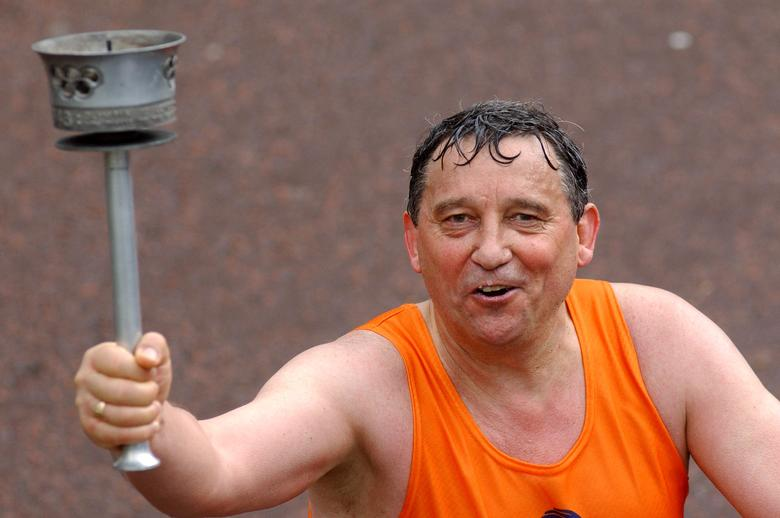 Former England soccer manager Graham Taylor crosses the finish line of the 2004 London Marathon, Britain April 18, 2004. REUTERS/David Bebber/File Photo