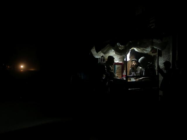 A Palestinian man sells falafel in a makeshift shop lit with a lamp powered by a battery during a power cut in Beit Lahiya in the northern Gaza Strip January 11, 2017. Picture taken January 11, 2017. REUTERS/Mohammed Salem