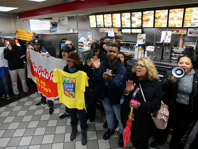 Local fast food workers take part in nationwide protests to denounce President-elect Donald Trump's nomination of Andy Puzder, a restaurant mogul who owns Carl's Jr. and other chains, as U.S. Secretary of Labor inside a Carl's Jr. restaurant in Los Angeles, California, U.S., January 12, 2017.  REUTERS/Mike Blake