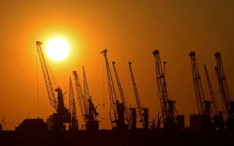 Cranes of German shipyard Blohm&Voss are silhouetted against the setting sun in Hamburg July 22, 2013. REUTERS/Fabian Bimmer