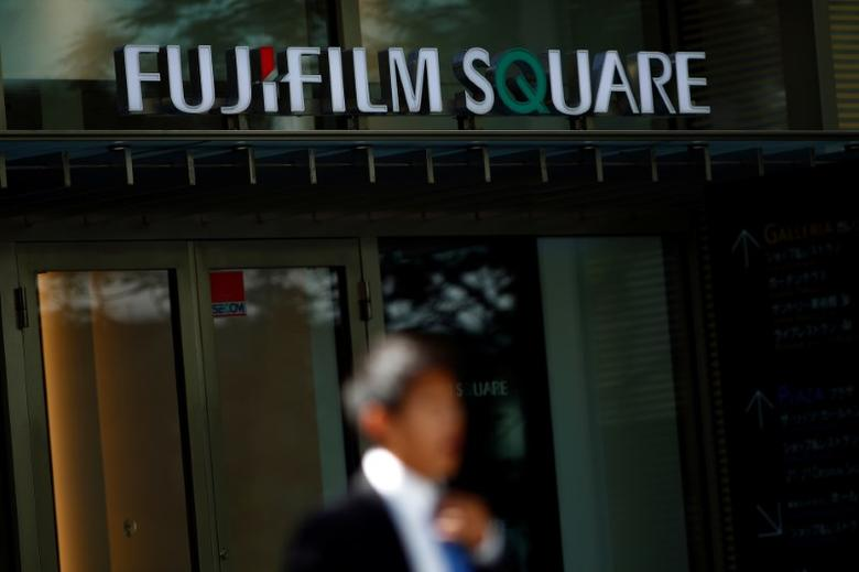 A man stands in front of the headquarters of Fujifilm Holdings Corp in Tokyo, Japan, June 2, 2016. REUTERS/Thomas Peter