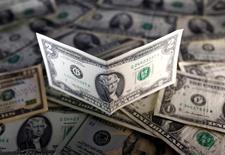 Долларовые купюры. Доллар США сохранил преимущество к другим валютам, набранное после комментариев главы американского Федрезерва Джанет Йеллен, указывающих на возможное быстрое повышение ставок в текущем году. REUTERS/Dado Ruvic/Illustration