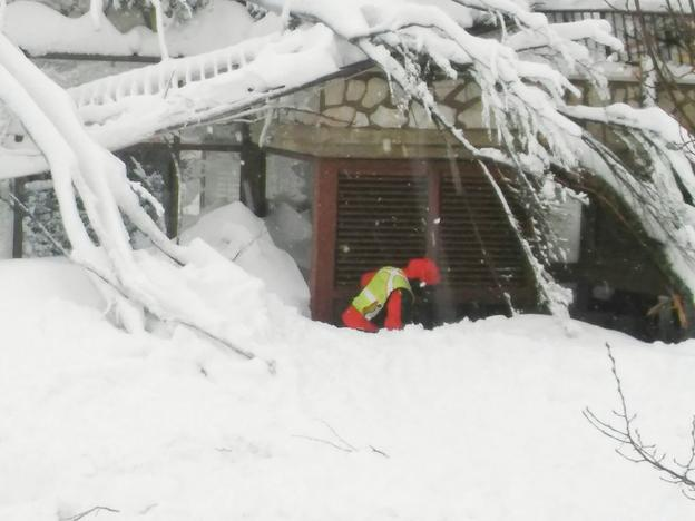 A member of Lazio's Alpine and Speleological Rescue Team is seen in front of the Hotel Rigopiano in Farindola, central Italy, hit by an avalanche, in this January 19, 2017 handout picture provided by Lazio's Alpine and Speleological Rescue Team. Soccorso Alpino Speleologico Lazio/Handout via REUTERS